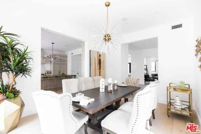 Bright dining room with white cushioned chairs and a dark wood dining table lighted by a sunburst chandelier. It includes a brass dining cart on the side along with a large geometric vase filled with green plants.