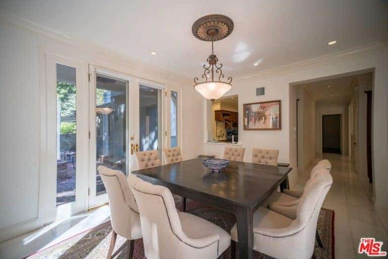 Neutral dining room decorated with framed wall art and an ornate pendant light that hung over the wooden dining table topped with a ceramic bowl. It has beige tufted chairs and a French door leading out to the porch.