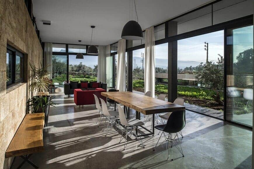 An open dining area with concrete flooring and full height glazing overlooking the lush greenery. It includes a dome pendant light and a wooden dining table surrounded by contrasting white and black chairs.