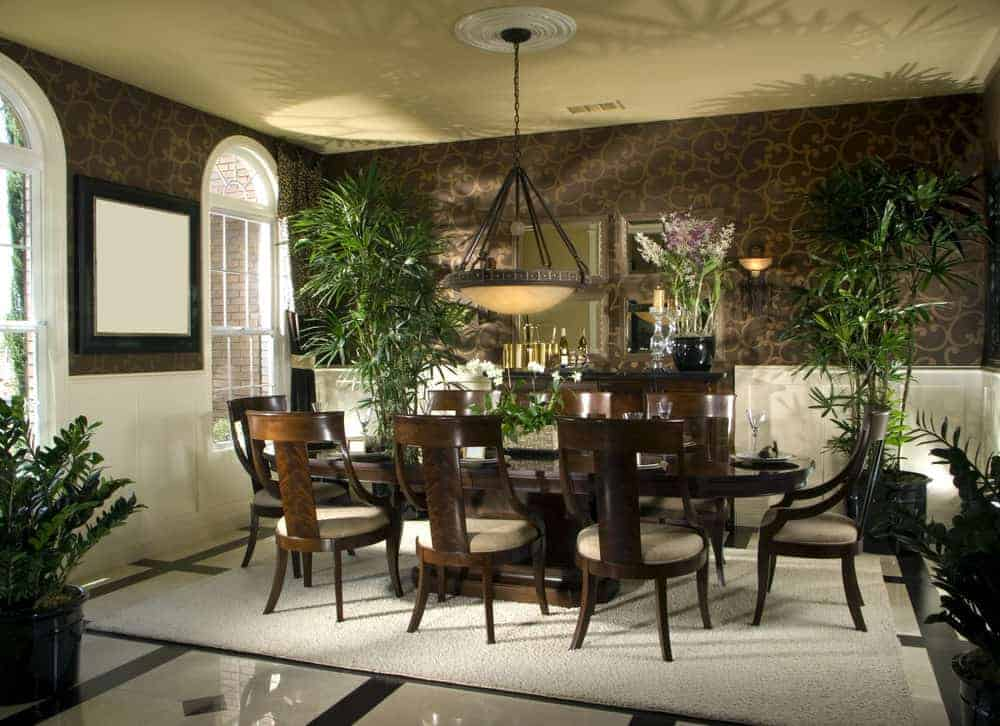The tropical dining room showcases an oversized pendant light and wooden dining set for eight that sits on a beige area rug. It has tiled flooring and arched windows inviting natural light in.