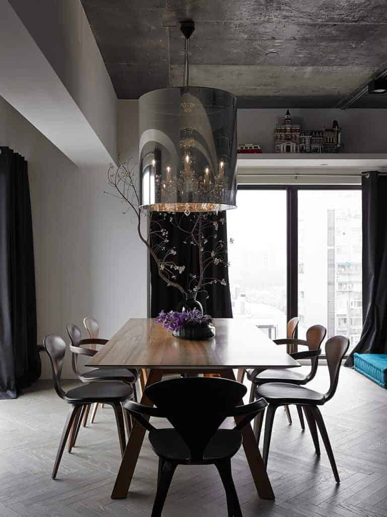 Dark dining room features stylish chairs and a wooden dining table topped with lovely plant centerpiece. It has herringbone flooring and rustic ceiling with a hanging drum pendant light.