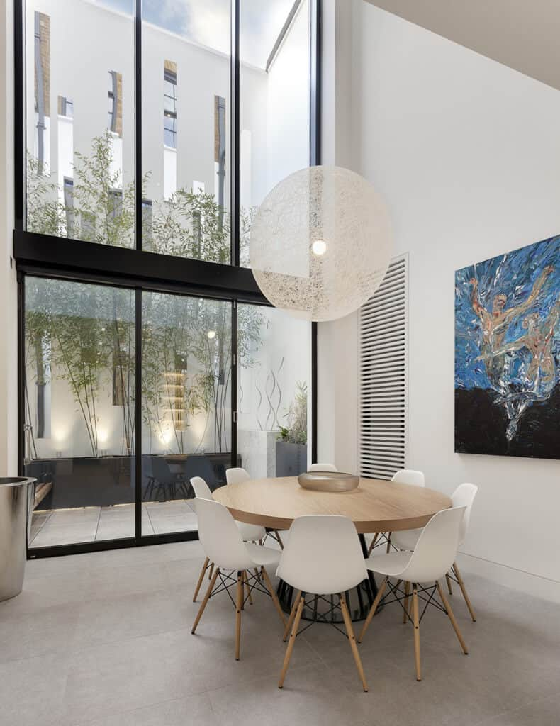 An oversized round pendant hangs over the wooden dining table in this high ceiling dining room with modern chairs and a canvas painting mounted on the white wall.