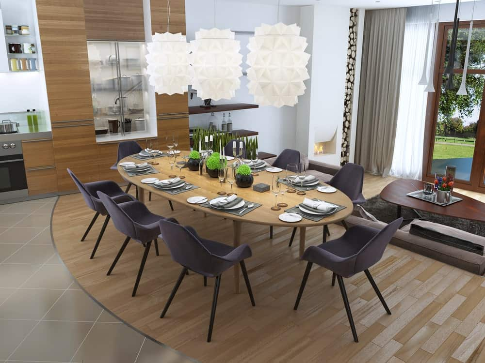 An open dining area with stylish white pendant lights, modern chairs and an oval dining table that complements the wood plank flooring.