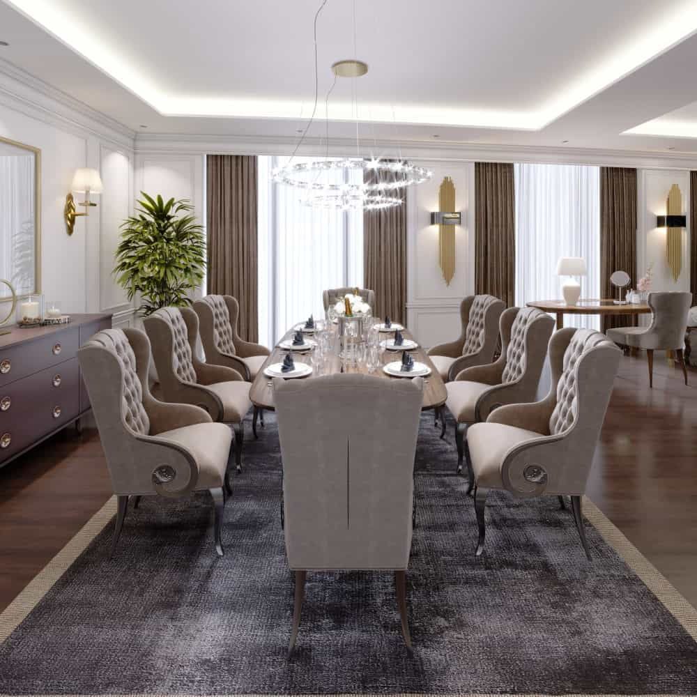 The classy dining room features wooden dining table and beige tufted wingback chairs on a bordered area rug. It is lighted by a two-tier round chandelier that hung from the tray ceiling beige tufted wingback chairs on a bordered area rug. It is lighted by a two-tier round chandelier that hung from the tray ceiling.