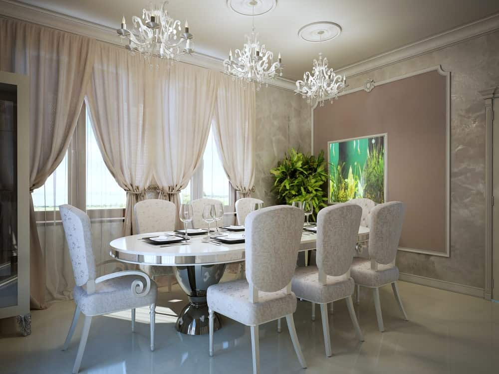 Elegant dining room with gorgeous dining set for eight illuminated by fabulous chandeliers. There's a potted plant in the corner that brings a refreshing ambiance in the room.