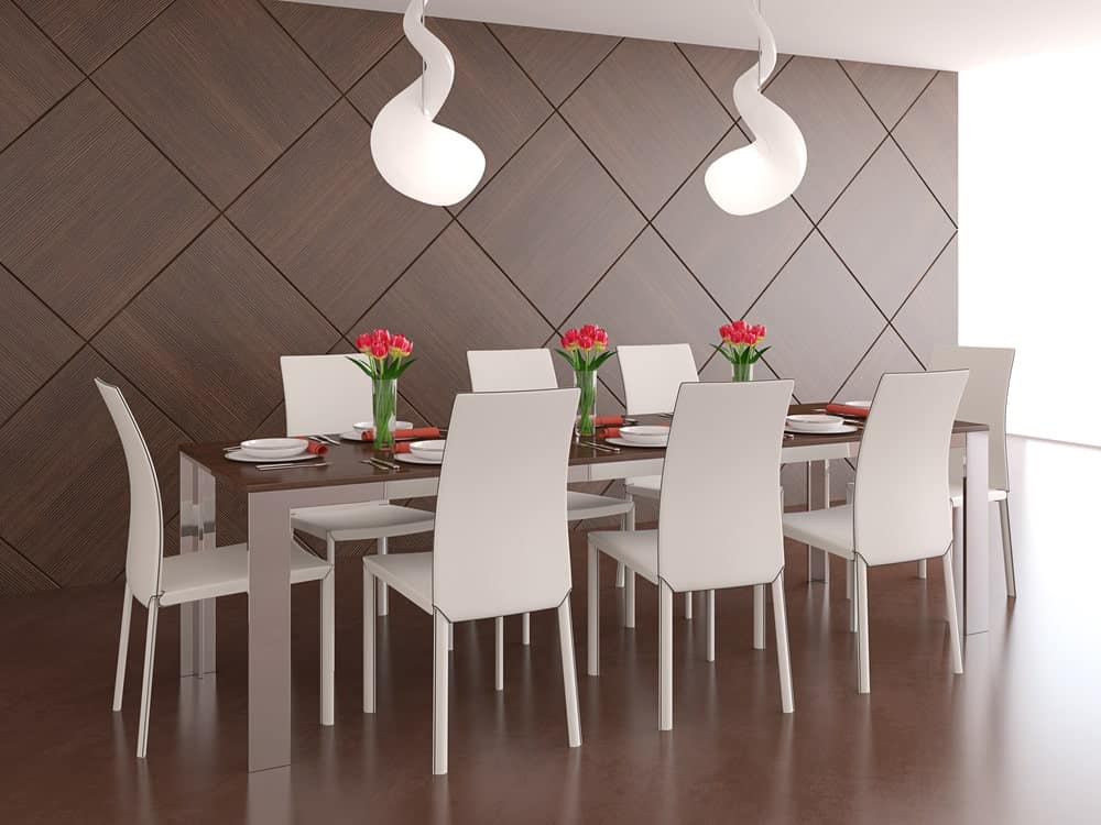 Modern dining room with smooth brown flooring and wood paneled wall arranged in diamond pattern. It includes a pair of twirl pendant lights that hung over the long dining table surrounded by sleek white chairs.