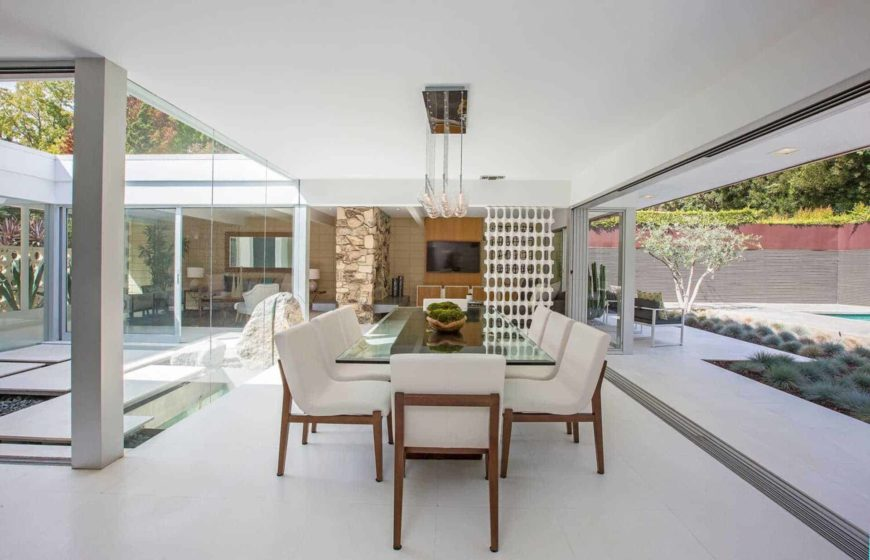 Serene dining room with tiled flooring and full height glazing bringing plenty of natural light in. It has sleek white chairs and a glass top dining table illuminated by globe pendant lights.