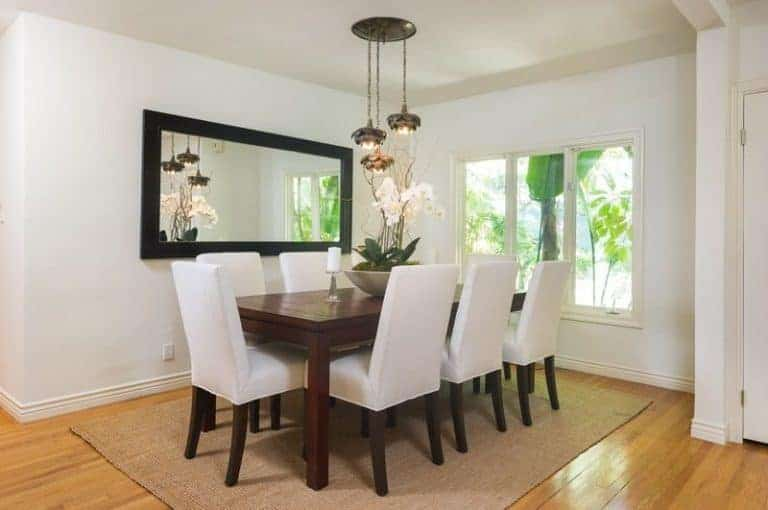 White dining room offers a three-panel window and a black framed mirror mounted across the dark wood dining table and white upholstered chairs over a jute area rug.
