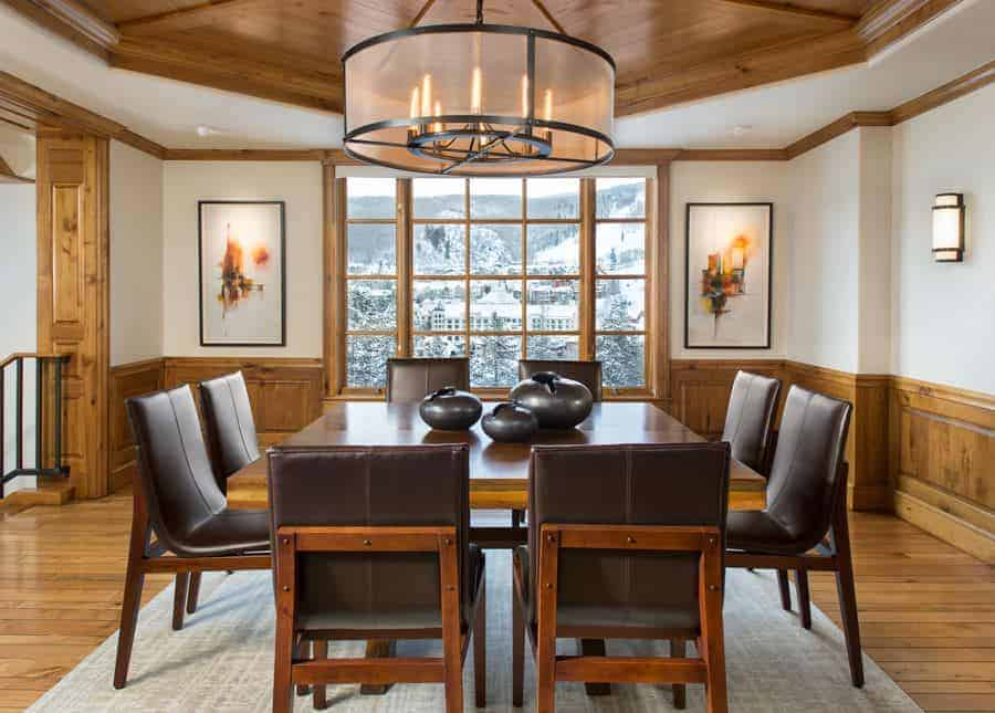 A large drum pendant light illuminates this dining room offering leather chairs and a square dining table topped with black vases. It includes lovely wall arts and a gray area rug that lays on the wood plank flooring.