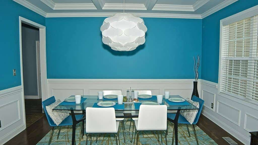 Blue dining room designed with white wainscoting and coffered ceiling with a hanging pendant light. It has a glass top dining table and modern chairs that sit on a blue area rug.