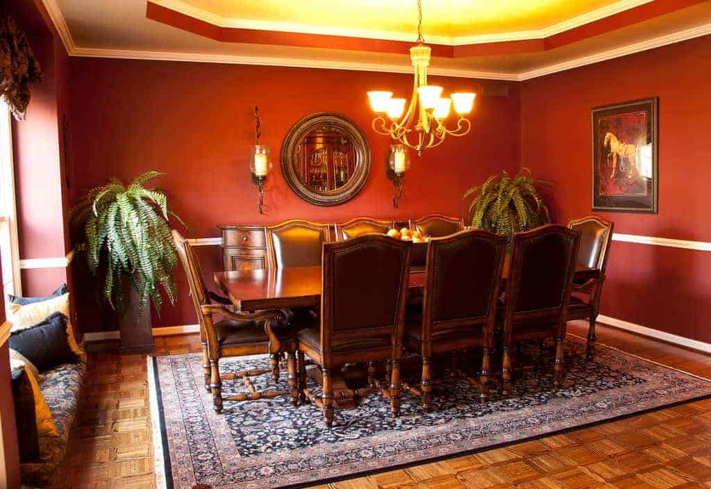 A pair of ferns on pedestals create a tropical vibe in this red dining room boasting a vintage chandelier and a wooden dining set paired with black leather chairs. It includes a classic area rug and a round mirror flanked by wall sconces.