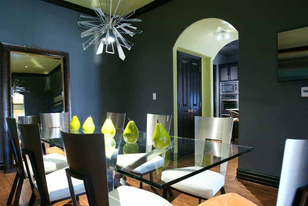 Cushioned dining chairs sit at a glass top table lined with green pears in this dining room with a glass sunburst chandelier and a rectangular mirror that creates a larger visual space in the area.