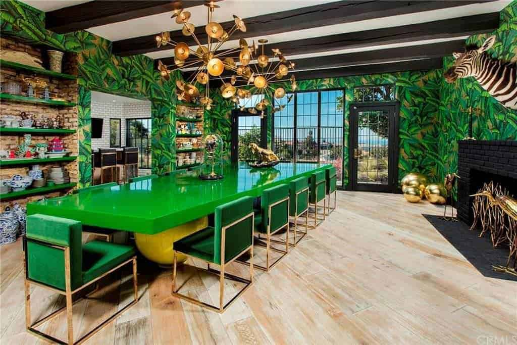 Eclectic dining room incorporated with a safari theme features a gorgeous green dining set situated in between brick inset shelves and black fireplace. It is illuminated by brass sputnik chandeliers that hung from the wood beam ceiling.