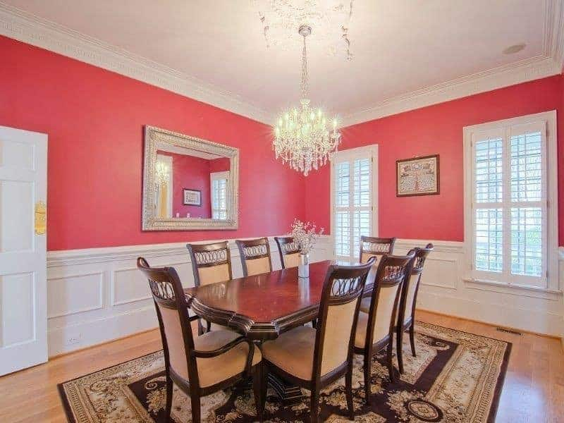 Pink dining room decorated with framed wall art and mirror mounted above the white wainscoting. It has a dark wood dining set on a black bordered rug lighted by a fancy crystal chandelier.