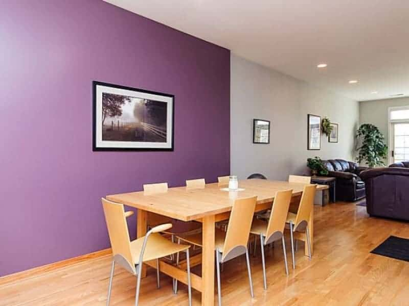 A wooden dining set for eight complements with the hardwood flooring in this simple dining room showcasing a purple accent wall mounted with a black framed landscape.