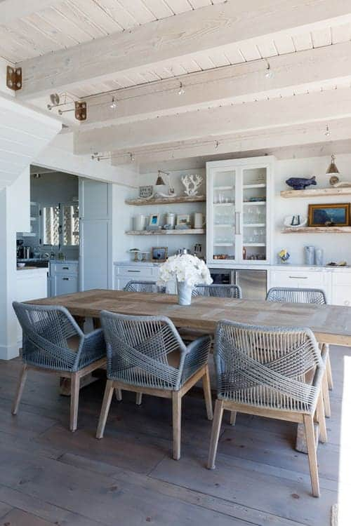 Beach style dining room with a rectangular dining table and gray woven chairs over natural wood plank flooring. It is illuminated by track lights mounted on the wood beam ceiling.