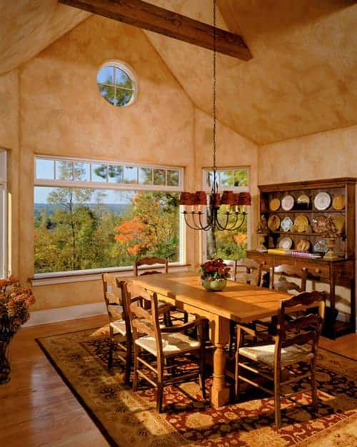 Warm dining room showcases a wooden dining set and a display cabinet filled with decorative plates. It has a cathedral ceiling and picture windows framing the outdoor scenery.