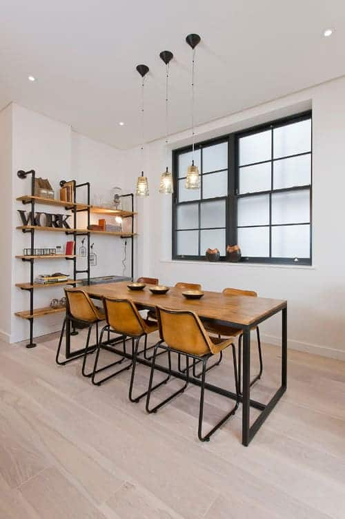 Glass pendant lights hang over the metal dining set complementing with the built-in shelving filled with books and decors. It has light wood plank flooring and frosted glass windows framed in aluminum.