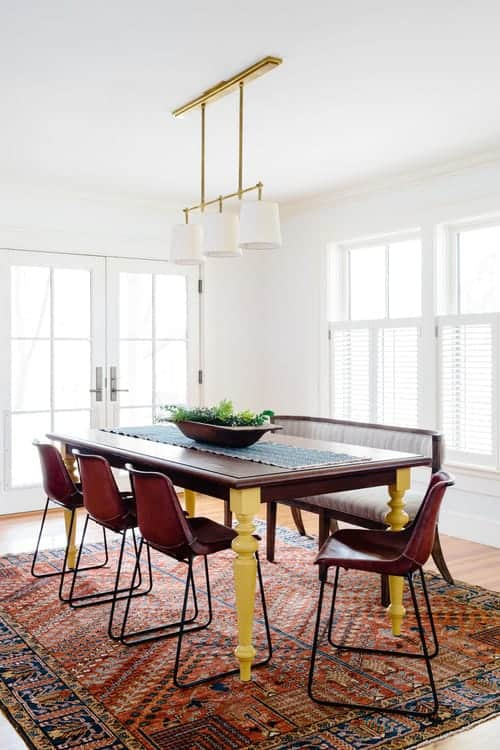A brass pendant light hangs over the rectangular dining table topped with a blue runner and potted plant. It is surrounded by a striped bench and red metal chairs over the patterned area rug.
