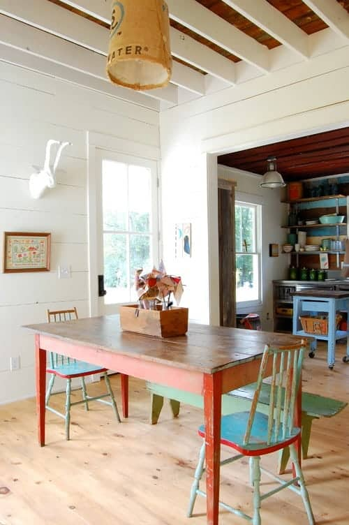 Farmhouse dining room showcases shiplap walls and wood beam ceiling with a hanging pendant light. It includes a wooden dining table accompanied by distressed green chairs and bench.