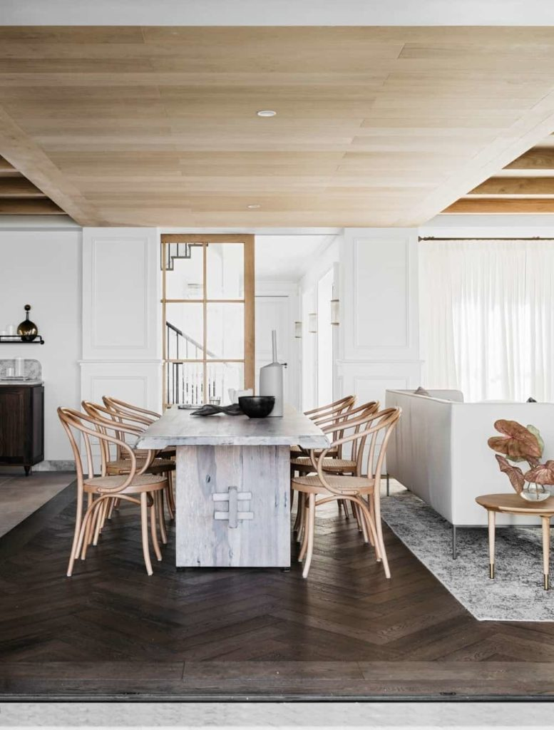 A dining space situated behind the living area showcases a rustic dining table and wicker round back chairs. It has herringbone wood flooring and wood paneled ceiling fitted with recessed lights.