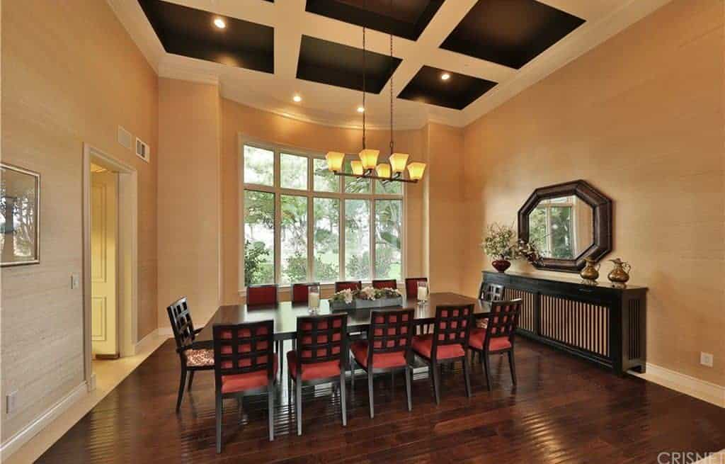 Red cushioned chairs stand out in this beige dining room with a rectangular dining table and a warm pendant light that hung from the black coffered ceiling. It includes a dark wood buffet table accented with a flower vase and an octagonal mirror.