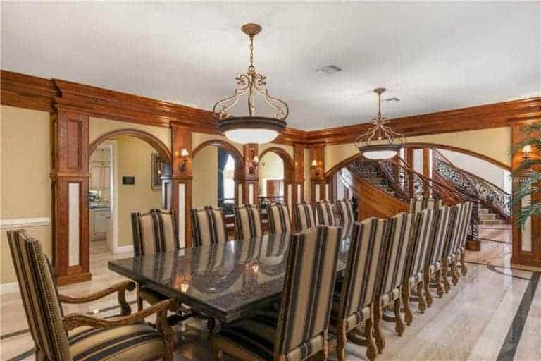 Classy dining room offers striped high back chairs and a long granite top table lighted by a pair of round pendants. It is surrounded by open archways and wall sconces mounted on the wood paneled columns.