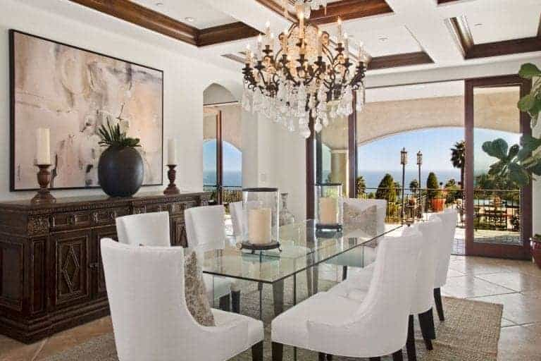 Elegant dining room with a glass top dining table and white wingback chairs that sit on a wicker area rug. It is accompanied by a glamorous chandelier and a carved wood buffet table highlighted by a large framed wall art.