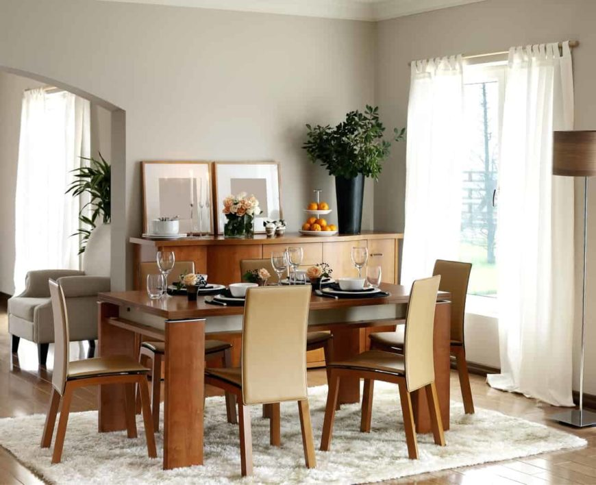 Beige leather chairs sit at a rectangular dining table in this fresh dining room with a shaggy area rug and a wooden buffet table topped with framed wall arts and potted plants.