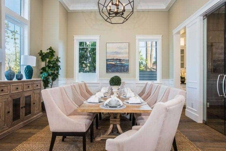 This dining room showcases a rectangular dining table and blush velvet chairs illuminated by a geometric chandelier that hung from the tray ceiling. It has a jute area rug and a wooden buffet table topped with blue vases and lampshade.