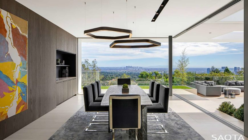 Modern dining room illuminated by a pair of hexagonal pendants that hung over the granite dining table surrounded with black leather chairs. It is enclosed in a wood paneled wall and panoramic windows overlooking an amazing outdoor view.