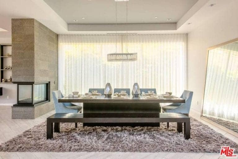 Stylish dining room designed with a linear chandelier and geometric centerpieces that sit on the rectangular dining table paired with light blue upholstered chairs and a dark wood bench.
