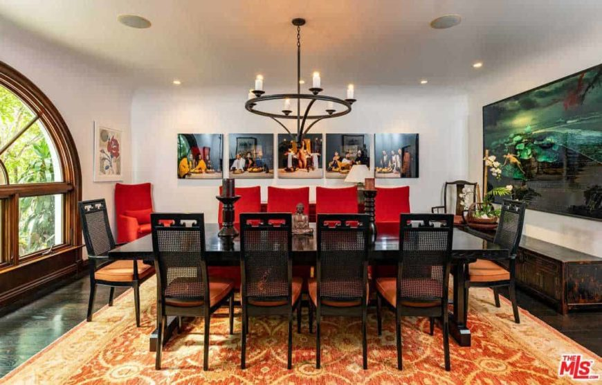 This dining room features multi-panel wall arts and an orange area rug that lays on the dark wood plank flooring. It has a rectangular dining table paired with red and orange cushioned chairs lighted by a wrought iron chandelier.
