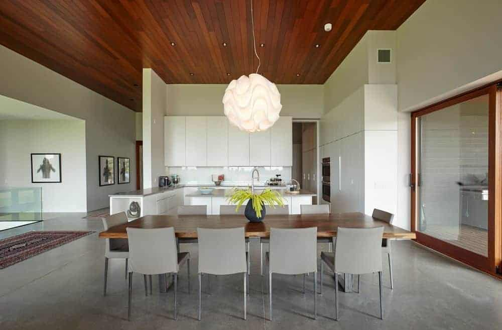 An open dining area features a wooden rectangular table and sleek gray chairs that complement with the concrete flooring. It is illuminated by a gorgeous round pendant and recessed lights fitted on the wood plank ceiling.