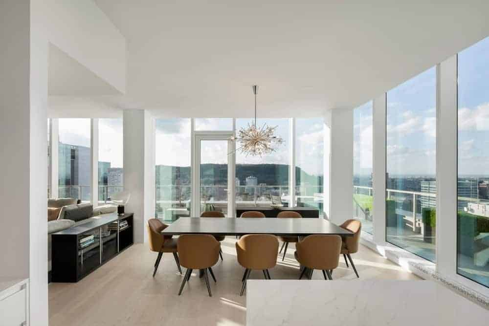 Bright dining area surrounded with floor to ceiling windows which bring plenty of natural light in. It has a stunning chandelier that hung over the dark wood rectangular table and brown round back chairs.