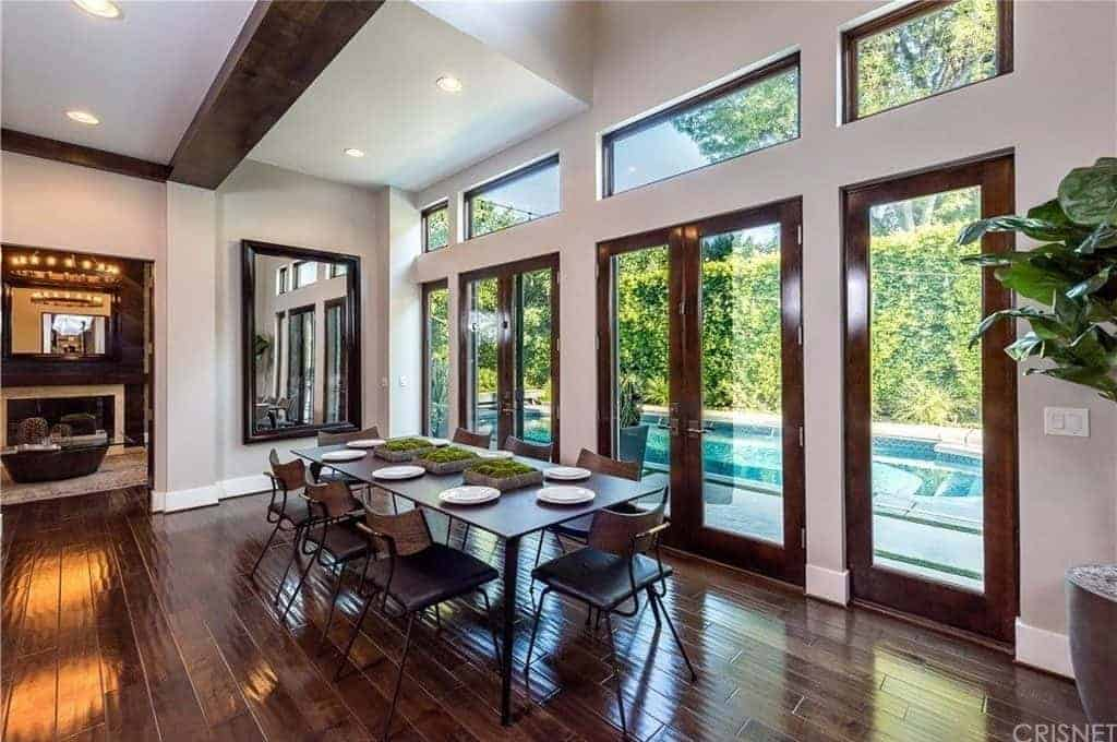 Fresh dining area with rich wood plank flooring and glass paneled windows overlooking the sparkling swimming pool. It includes a metal dining set and a large mirror mounted on the light gray wall.