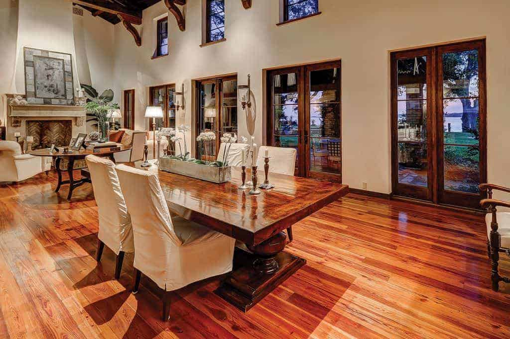Warm dining area features a glossy wooden table and white skirted chairs over the rich wood plank flooring. It is situated across the round table and chevron fireplace accented with lovely wall art.