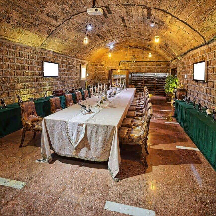 Marvelous dining room boasts a long dining set placed in between green skirted tables that are topped with bottled wines. It has brick walls and barrel vaulted ceiling mounted with track lights.