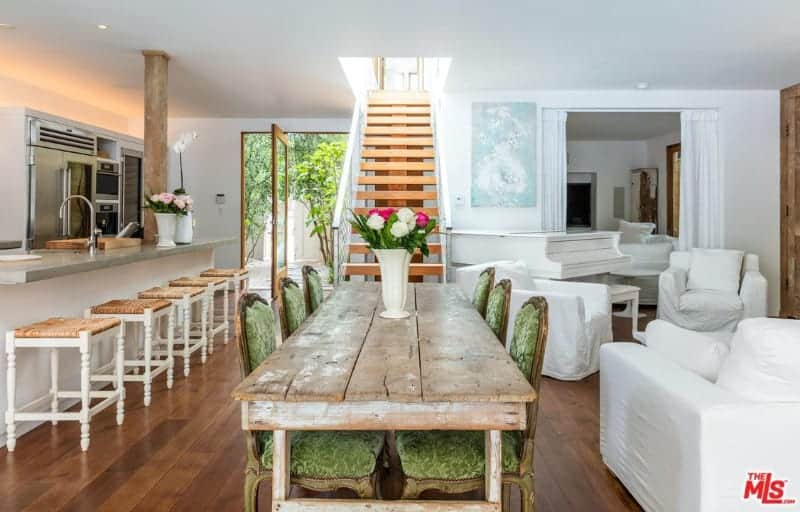 An open concept house with a dining space next to the straight staircase showcasing green upholstered chairs and a rustic dining table topped with a lovely flower vase. It is situated in between the kitchen and living area.
