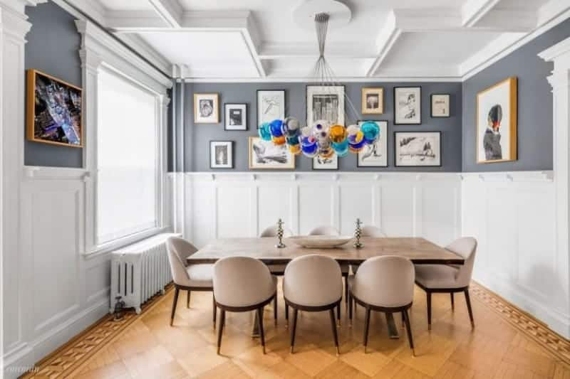 Multi-colored bubble chandelier hangs over the beige dining set in this formal dining room designed with gallery frames mounted above the white wainscoting.