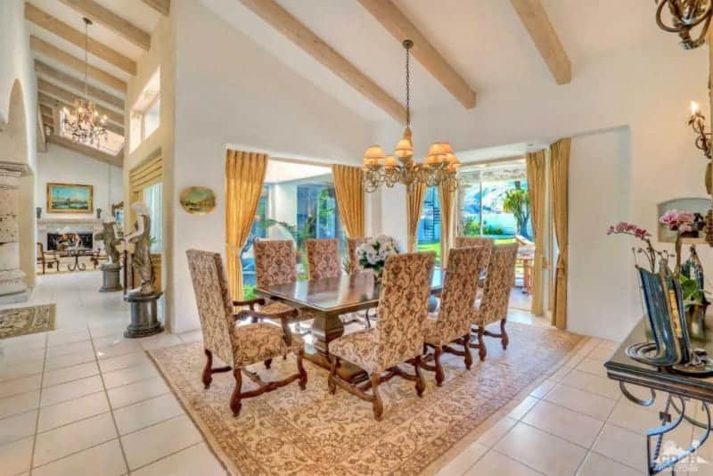 Classic dining area with a rectangular dining table and floral high back chairs complementing the patterned area rug on tiled flooring. It is illuminated by a warm chandelier that hung from the vaulted ceiling lined with wood beams.