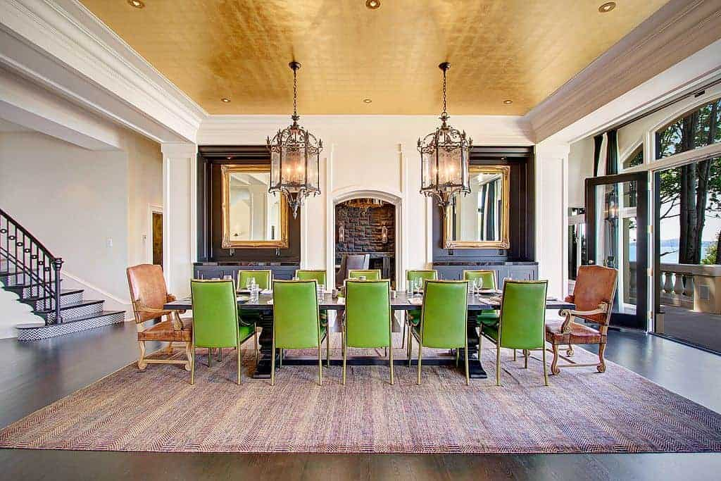 Green leather chairs add a nice accent in this eclectic dining room boasting gorgeous pendant lights and gold framed mirrors mounted above the built-in cabinets.