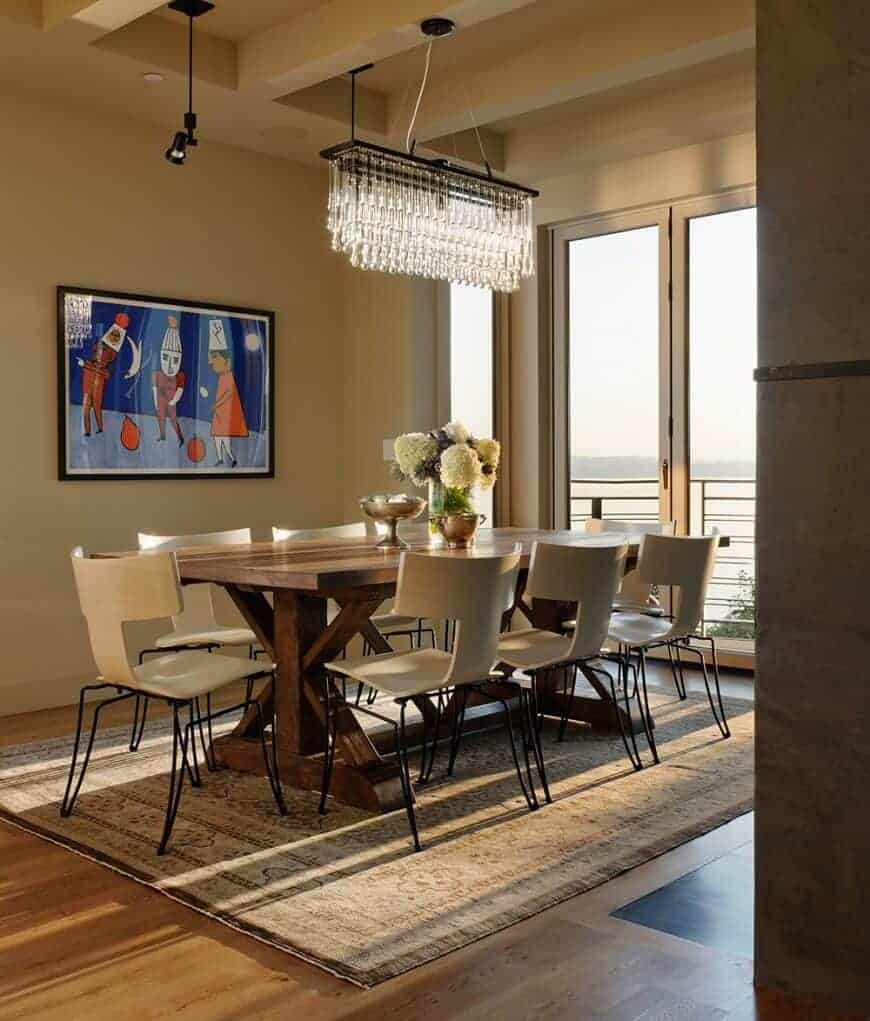 This dining room features a fancy linear chandelier and a cute wall art mounted across the wooden dining table and stylish white chairs that sit on a vintage area rug.