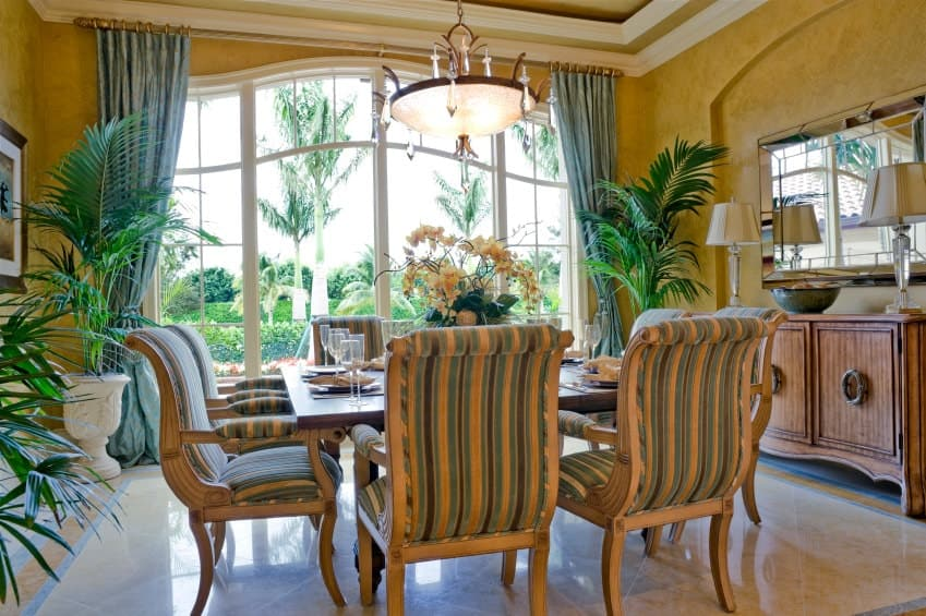 Tropical dining room with tiled flooring and full height windows allowing plenty of natural light in. It has a charming dining set and a wooden buffet table topped with lampshades and a bowl.