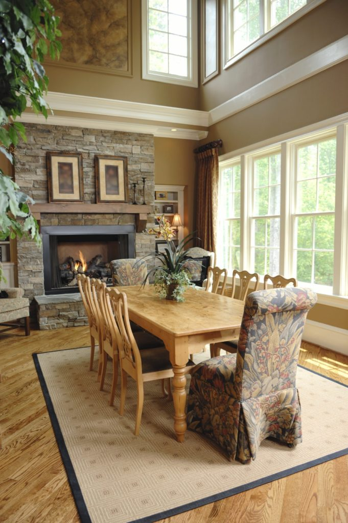A stone brick fireplace faces the wooden dining set in this high ceiling dining room with white framed windows and hardwood flooring topped by a beige area rug.
