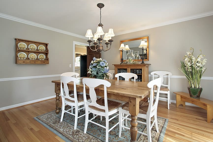 Gray dining room offers a glass front cabinet and floating shelf displaying ceramic plates with a unified design. It is illuminated by table lamps and a matching chandelier that hung over the wooden dining set on a charming blue rug.