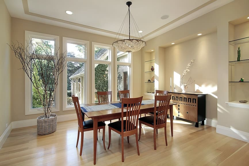 Bright dining room decorated with a twig tree and a dome chandelier that hung over the wooden dining table lined with a printed runner. It has black cushioned chairs and a console table placed in between inset shelves.