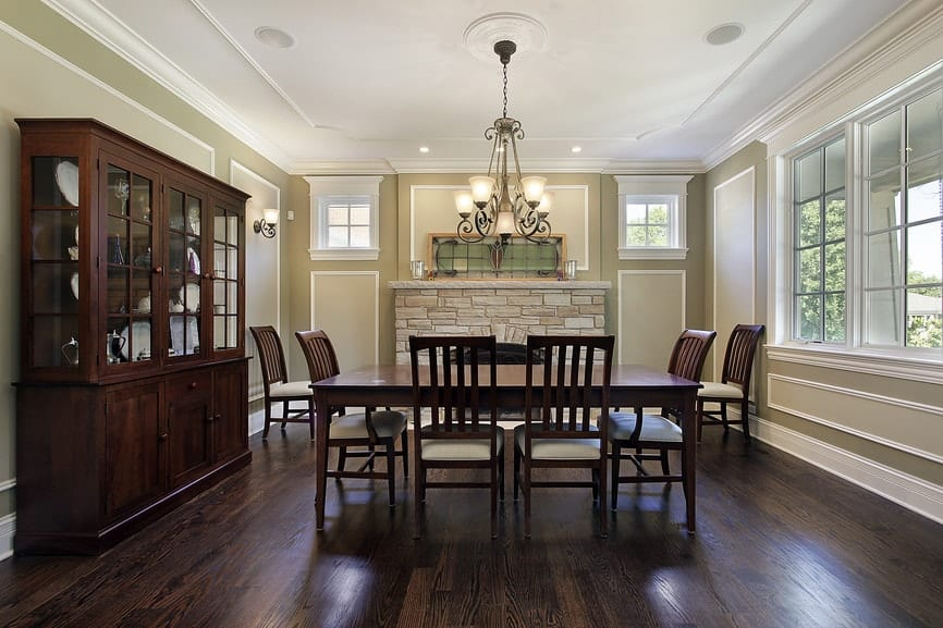 Formal dining room features full height wainscoting and dark wood plank flooring complementing with the wooden dining set and china cabinet. It includes an ornate chandelier and brick fireplace topped with a stained glass panel.