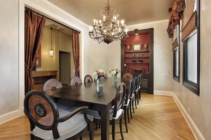 Sophisticated dining room showcases an inset shelf and a gorgeous candle chandelier that hung over the rectangular dining table surrounded by cushioned round back chairs.