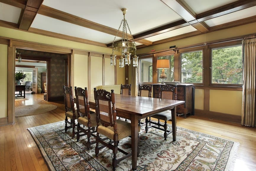 A traditional lampshade sits on a wooden buffet table in this dining room with a brass chandelier and a wooden dining set over a tasseled area rug.